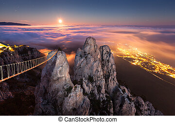 Beautiful night landscape with full moon, sea, rocks and clouds
