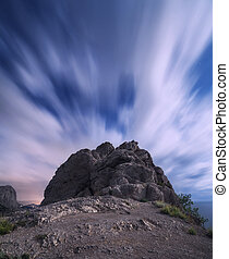 Beautiful night landscape with rocks against moving clouds