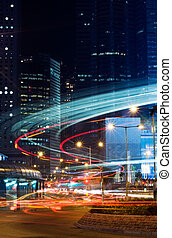 Beautiful night scenes of skyscraper with light and motion blurred of cars in Hong Kong.