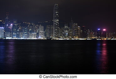 Beautiful night view of Hong Kong island skyline across Victoria Harbour from Avenue of Stars at Kowloon. Skyscrapers on waterfront in downtown. Global financial center.