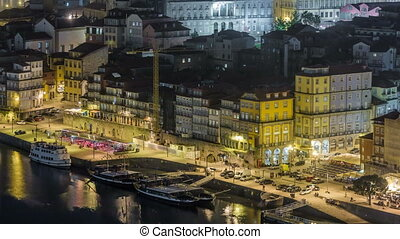 Beautiful night view of the Douro River timelapse and the embankment of the historic centre of Porto city on the blue sky background in Portugal at summer time.