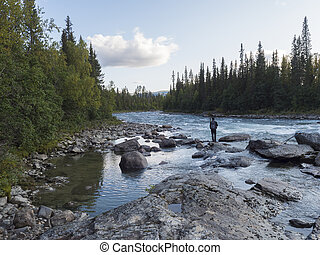 Beautiful northern landscape with wild glacial river Kamajokk, boulders and spruce tree forest in Kvikkjokk in Swedish Lapland. Summer sunny day, golden hour, dramatic clouds.
