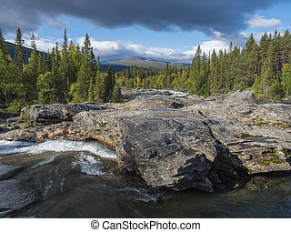 Beautiful northern landscape with wild glacier river Kamajokk, boulders and spruce tree forest in Kvikkjokk in Swedish Lapland. Summer sunny day, golden hour, dramatic clouds.