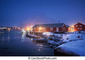 Beautiful norwegian Rorbu on sea cost and snowy mountain at night