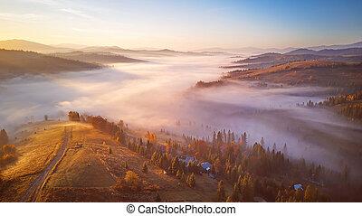 Beautiful November sunrise over mountain foggy valley.