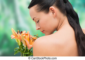 Beautiful nude brunette smelling bunch of lilies on blue and...