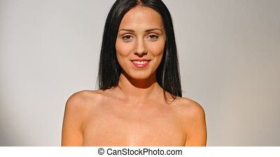 Beautiful nude woman in studio smiling to camera