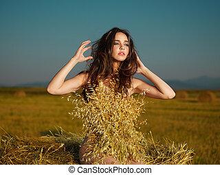 beautiful nude woman posing on hay stack