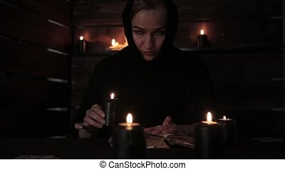 Beautiful nun holds a candle and reading old book of highlights the flame. Christianity concept