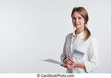 Beautiful nurse smiling and taking notes on a white isolated background