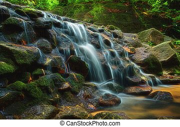 Beautiful of small waterfall flowing over the rock in the forest.