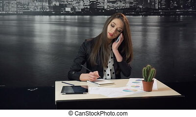 A studio shot of a beautiful smiling woman works in economical sphere. Young brunette uses smartphone and tablet pc in office work before city wallpaper. 100FPS shot, slowmotion