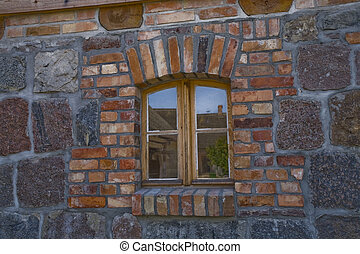 old antique window in a wooden frame in a historic brick building in close-up