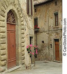 Beautiful old arch doorway on tuscan narrow street in small...