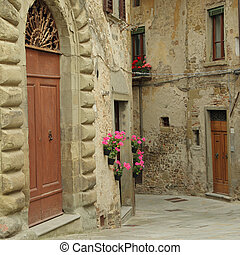 Beautiful old arch doorway on tuscan narrow street in small...