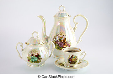 Beautiful old coffee pot, sugar-basin and cup with a drawing