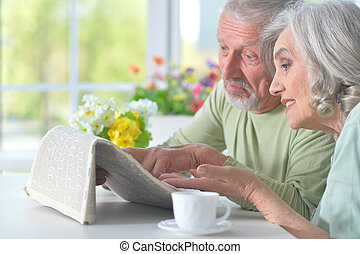 Beautiful old couple reading a newspaper