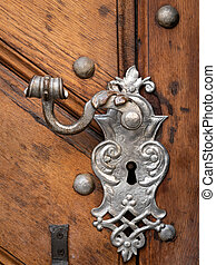 Beautiful old doorhandle and decoration made of silver on a brown door