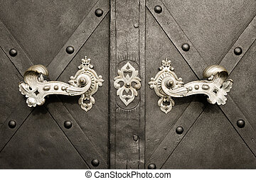 Beautiful old doorhandles and decoration made of silver on a dark door