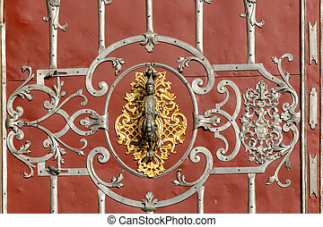 Beautiful old doorknob made of silver and gold on a red door