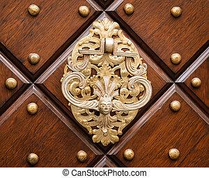 Beautiful old doorknob made of silver on a brown door