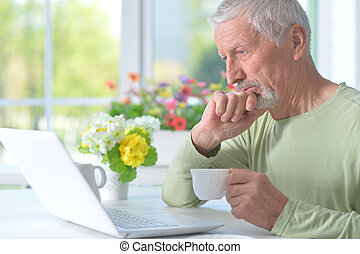 Beautiful old man with a laptop