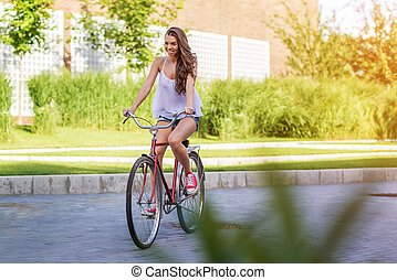 Beautiful old woman with bicycle in a park