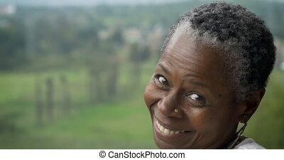 Beautiful older African American woman in her 60s flirting...
