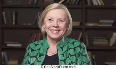 Beautiful older blonde woman smiling, bookshelf background