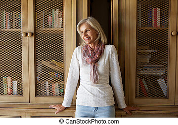 beautiful older woman leaning against bookcase at home
