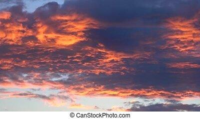 Beautiful orange and dark blue curling clouds above sunset...