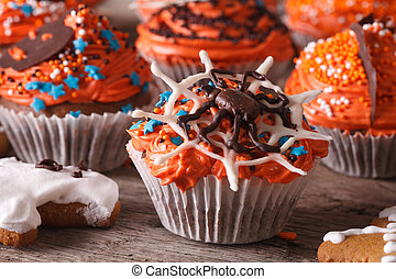Beautiful orange Halloween cupcakes with spider close-up. Horizontal