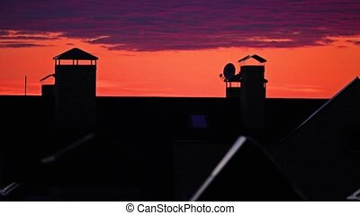 Beautiful orange sky and purple sunset clouds move over town sloping roofs. 4K evening time lapse