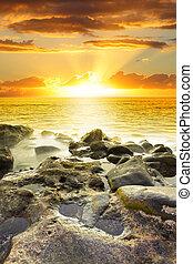 Beautiful orange sundown at rocky beach. Water in motion blur.