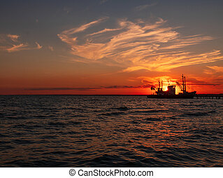 Beautiful orange sunset on sea water. Transport ship on the dock in the evening on seacoast. Shipping logistic by sea.