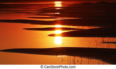 beautiful orange sunset with waved river sand beach