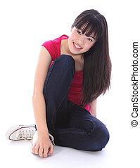 Beautiful oriental teenager girl sitting on floor