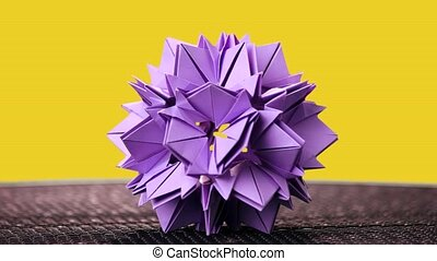 Beautiful origami flower on yellow background. Floral paper...