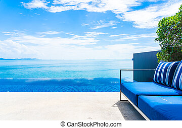 Beautiful outdoor swimming pool with sea ocean on white cloud blue sky background decoration with pillow sofa