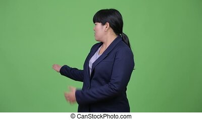 Beautiful overweight Asian businesswoman presenting...