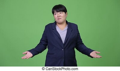 Beautiful overweight Asian businesswoman shrugging - Studio...