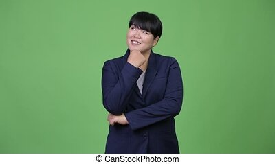 Beautiful overweight Asian businesswoman smiling while...