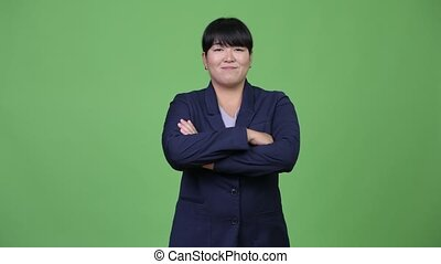 Beautiful overweight Asian businesswoman smiling with arms...