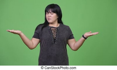 Beautiful overweight Asian woman comparing something -...