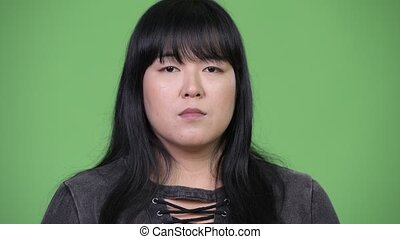 Beautiful overweight Asian woman covering ears as three wise...
