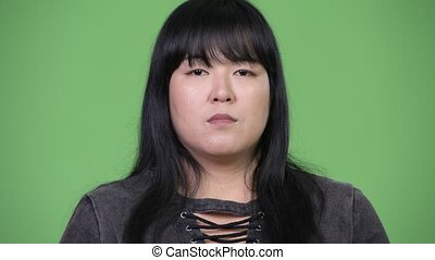 Beautiful overweight Asian woman covering mouth as three...
