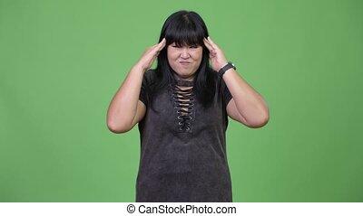 Beautiful overweight Asian woman having headache - Studio...