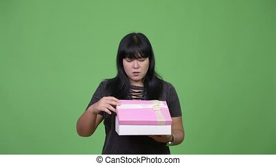 Beautiful overweight Asian woman opening gift box and...