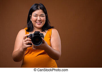 Beautiful overweight Asian woman photographer smiling happily