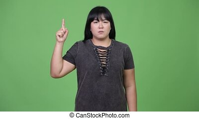 Beautiful overweight Asian woman pointing finger up - Studio...